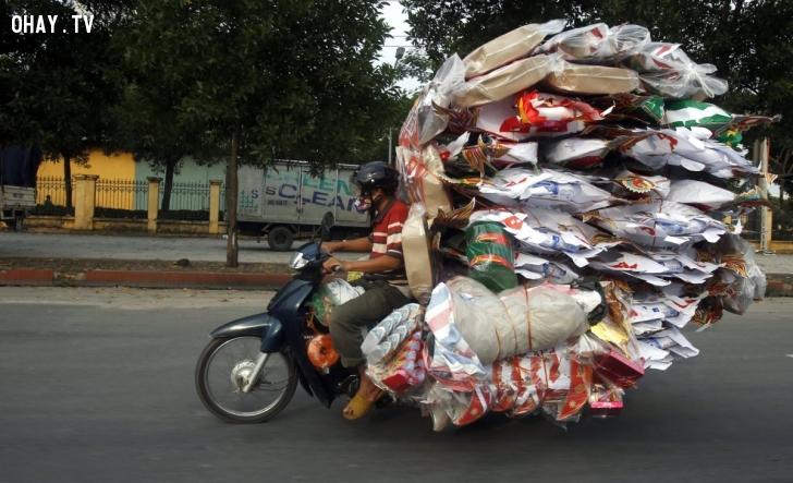Bức ảnh do phóng viên hãng tin Reuters chụp một người đàn ông đang chở hàng mã cồng kềnh trên chiếc xe máy để đem bán trong dịp lễ Vu Lan. Reuters cho biết một trong những tín ngưỡng của người Việt là đốt hàng mã để gửi những vật dụng sinh hoạt tới người cõi âm.
