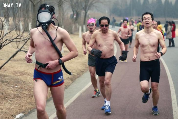 Một người Trung Quốc đeo mặt nạ bảo hộ khi tham gia cuộc thi chạy tại một công viên ở Bắc Kinh hồi tháng 2/2014. Cuộc thi nhằm khuyến khích người dân xây dựng lối sống lành mạnh và thân thiện môi trường. Bắc Kinh đã phát mức cảnh báo màu da cam về ô nhiễm không khí trong khoảng thời gian này.