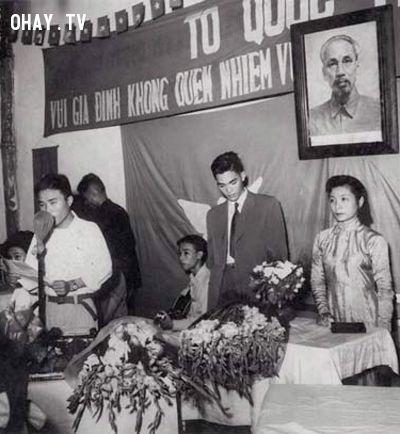 Một đám cưới tổ chức đơn giản, phông bạt cũng đơn sơ với ảnh Bác Hồ cùng dòng chữ vui gia đình không quên nhiệm vụ.
