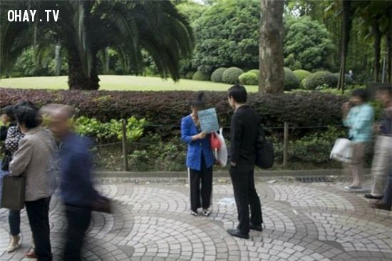 Một người đàn ông dừng lại đọc nội dung trên tấm biển của cô Su Jingjing