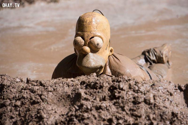 Một người tham gia lễ hội lợn bẩn truyền thống đeo khẩu trang Homer Simpson wallows trong một vũng lầy gần Hergisdorf, Đức 25/05/2015