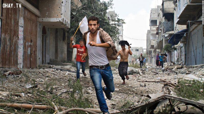 Người Palestine chạy trốn tên lửa của Israel, tay cầm cờ trắng tự tạo để ra dấu hiệu.
