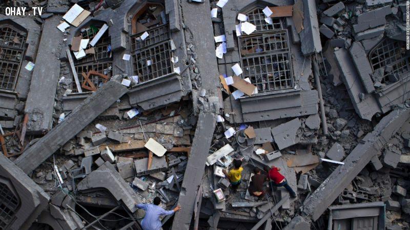 Người dân Palestine lục tìm những quyển kinh thánh trong đống đổ nát của nhà thờ Al-Qassam.