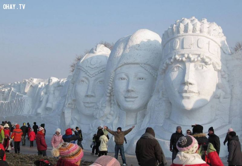 Snow sculpture of many different faces at Harbin in 2010
