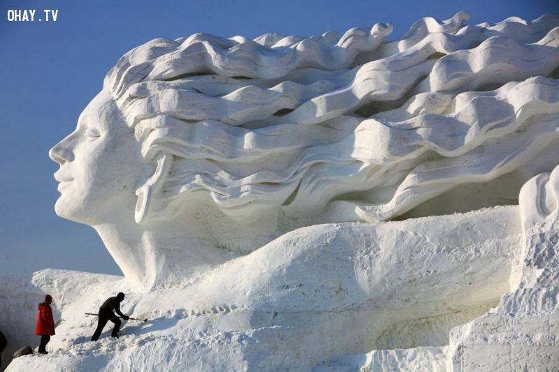 A snow sculpture of a woman whose hair is blowing in the wind