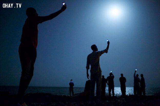 Những người đàn ông đang cố giơ cao điện thoại để thu sóng- Ảnh: National Geographic