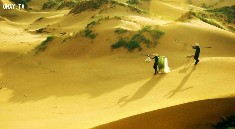 Ngư dân đi biển về qua đồi cát ở Bãi Môn - Ảnh: Dương Thanh Xuân