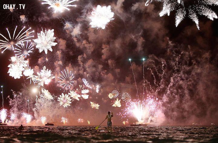 Anh chàng chèo thuyền xem pháo hoa giữa dòng sông