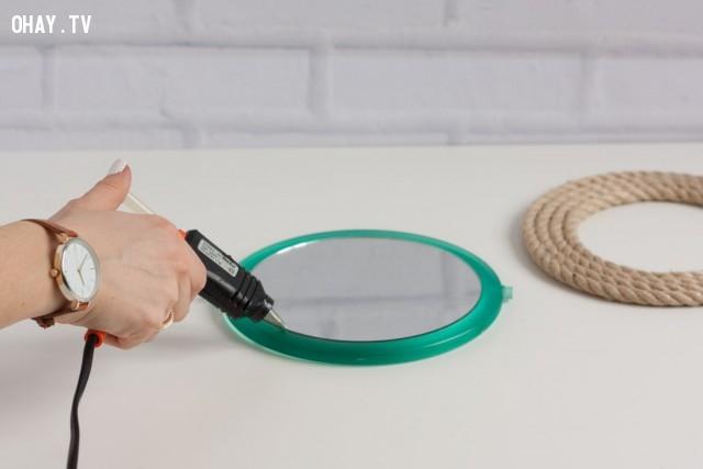 3. Trong thời gian chờ đợi vòng dây thừng khô keo. Bạn bắt đầu xịt keo nóng xung quanh khung gương để chuẩn bị đặt vòng dây thừng lên.,sản phẩm độc đáo,đồ handmade,mẹo vặt