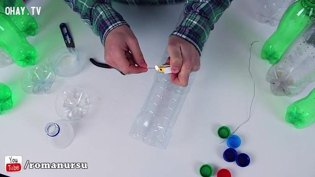 Sau đó bạn lồng hai phần chai nhựa vừa cắt xong vào nhau. Để cho hai đoạn chai nhựa dính vào nhau chắc chắn thì bạn dùng hơ kẽm trên lửa rồi xỏ vào rồi cột lại.,tái sử dụng chai nhựa,sản phẩm độc đáo,sản phẩm từ chai nhựa,mẹo vặt