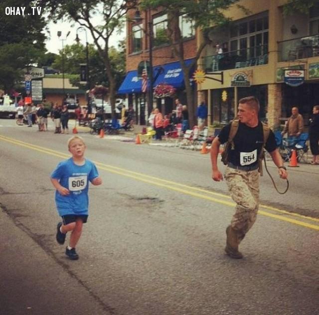 Một anh lính thủy Mỹ chạy theo cùng một cậu bé đang bị tụt lại phía sau nhóm chạy marathon,hình ảnh đẹp,cử chỉ đẹp