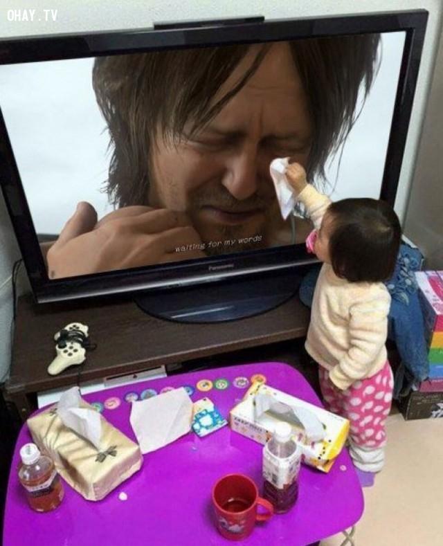 Cô bé lấy giấy lau nước mắt cho người đàn ông trên màn hình TV,hình ảnh đẹp,cử chỉ đẹp